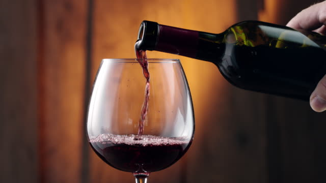 pouring red wine into glass - bottiglia video stock e b–roll