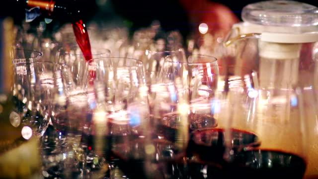 vídeos de stock e filmes b-roll de pouring red wine into the wine glasses. - copo vazio