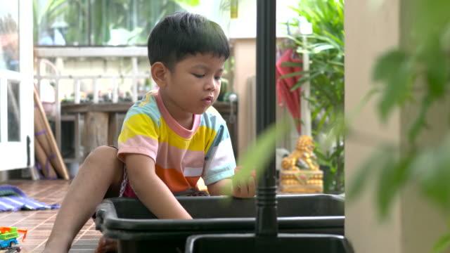 hälla sanden countinuously - endast en pojkbaby bildbanksvideor och videomaterial från bakom kulisserna