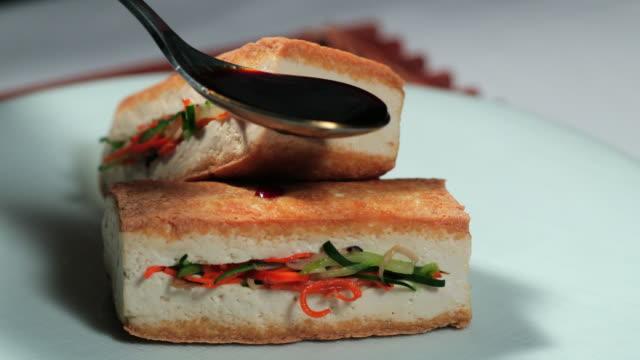 pouring sauce on 'dubusobagi' (korean temple food made with tofu) - korea stock videos & royalty-free footage
