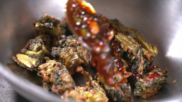 pouring sauce on 'siraegi gangjeong' (deep-fried dried radish leaves) - tradition stock-videos und b-roll-filmmaterial