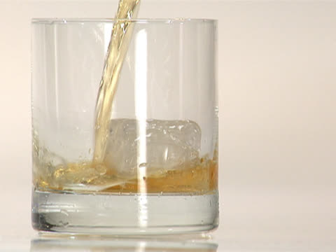 stockvideo's en b-roll-footage met pouring scotch into a glass with a single ice cube - middelenmisbruik