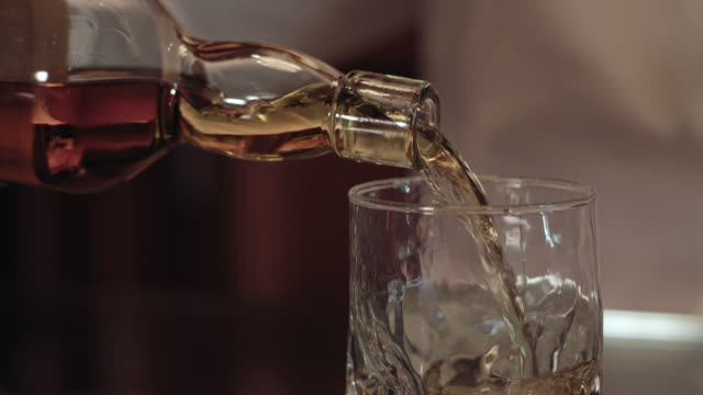 pouring scotch single malt whiskey from the bottle into a glass