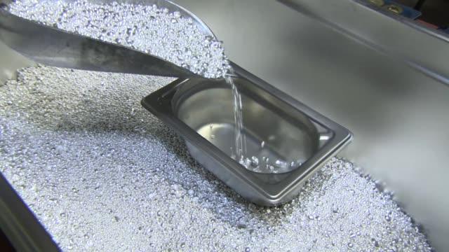 pouring silver granules into form - silverfärgad bildbanksvideor och videomaterial från bakom kulisserna