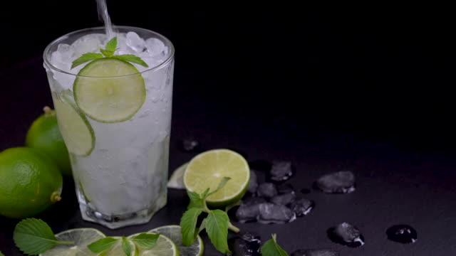 pouring soda into a glass drink with sliced lime - slow motion - traditional lemonade stock videos & royalty-free footage