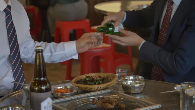 pouring soju (korean alcohol) at a company get-together - korean ethnicity stock videos & royalty-free footage