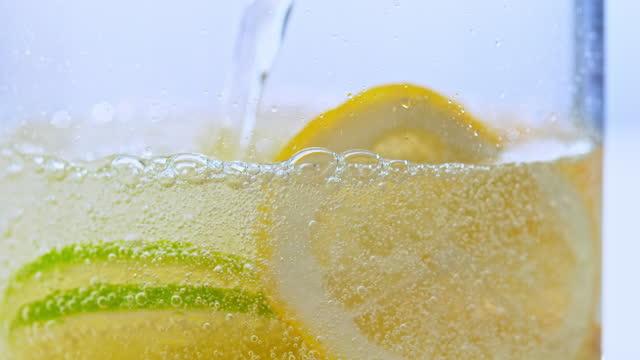 vidéos et rushes de slo mo ld verser de l'eau pétillante dans un verre avec des tranches de citron et de lime - quartier