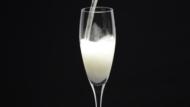 Pouring sparkling wine inside a glass