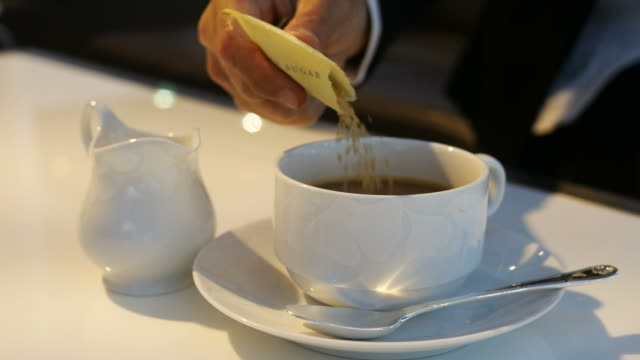 Pouring sugar into cup of hot coffee