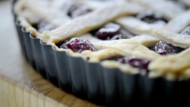 pouring sugar on a freshly baked cherry pie - tart dessert stock videos & royalty-free footage