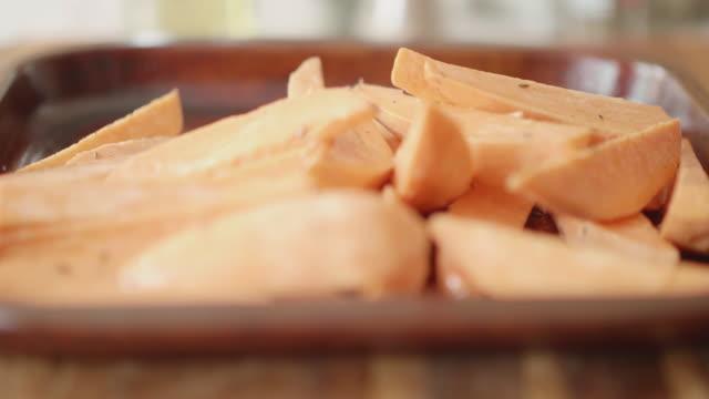 焙煎トレイにサツマイモのウェッジを注ぐ - サツマイモ点の映像素材/bロール