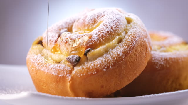 pouring syrup on to raisin - chocolate brioche buns - sliding shot - stuffed stock videos & royalty-free footage