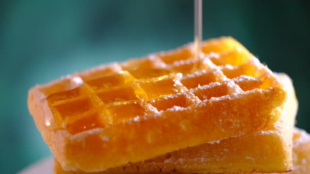 pouring syrup on to the powdered sugared waffles - pouring stock videos & royalty-free footage