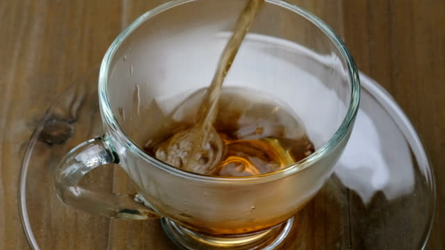 Pouring tea - Hot tea flowing from teapot to teacup