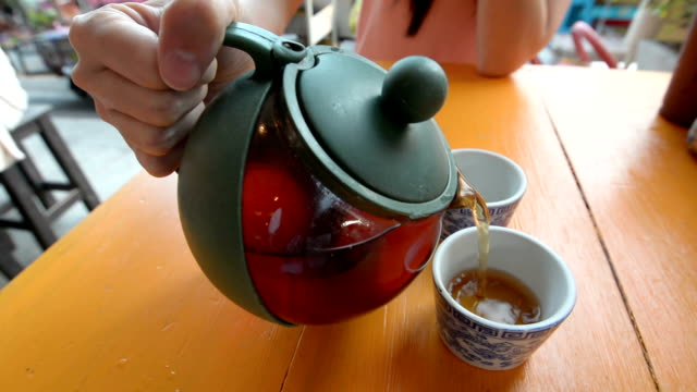 Pouring Tea in a Cup on Table