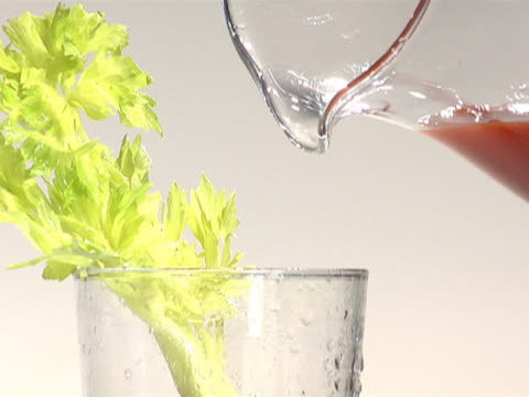 pouring tomato juice into a glass with a celery stalk - 注ぎ口点の映像素材/bロール