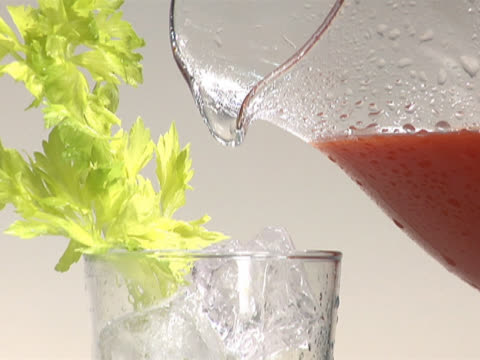 pouring tomato juice into a glass with ice and a celery stalk - 注ぎ口点の映像素材/bロール