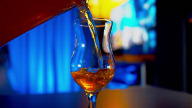 vídeos y material grabado en eventos de stock de verter jugo de fruta tropical en una copa de cóctel - cóctel tropical