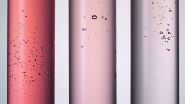 vidéos et rushes de pouring water creating bubbles in three scientific test tubes in a row with red and pink hues - beauté