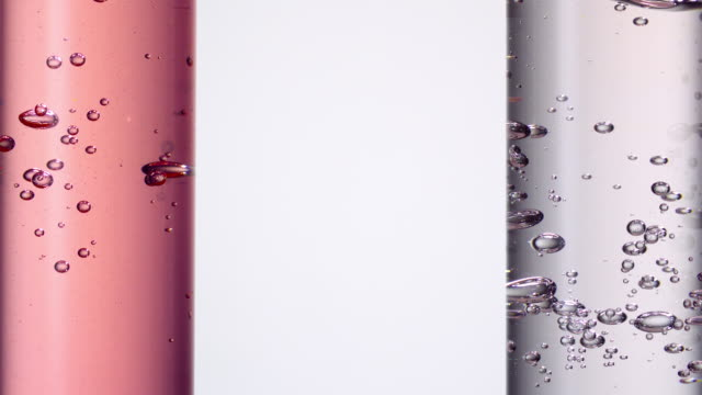 pouring water creating bubbles in two scientific test tubes in a row with red and pink hues, copy space in between - reagenzglas stock-videos und b-roll-filmmaterial