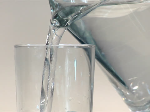 pouring water from a pitcher into a glass - 注ぎ口点の映像素材/bロール