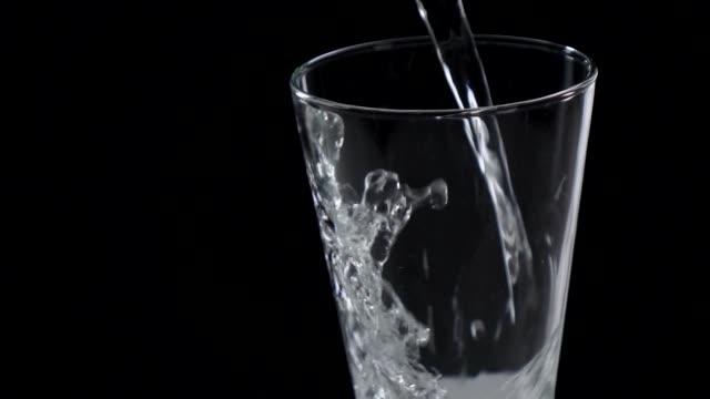 vídeos de stock e filmes b-roll de pouring water in a glass slow motion - copo vazio