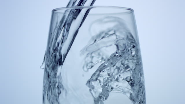 stockvideo's en b-roll-footage met pouring water in glass, slow motion-close up - drinkwater