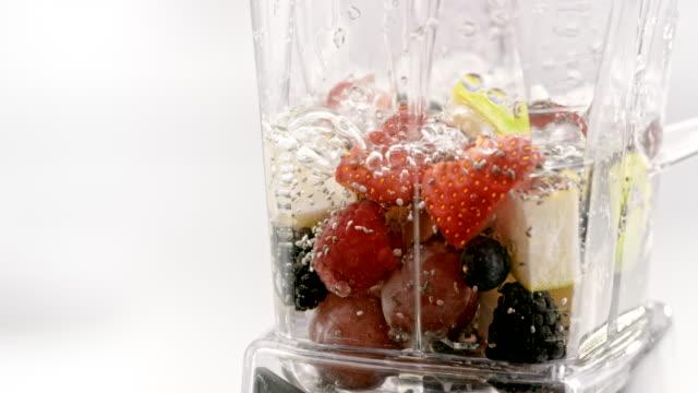 stockvideo's en b-roll-footage met slo mo ld gieten water in de blender met fruit - mixer