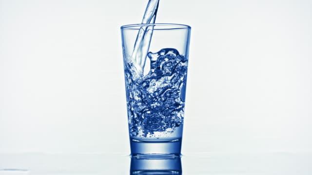 slo mo versare acqua in un bicchiere - super slow motion video stock e b–roll