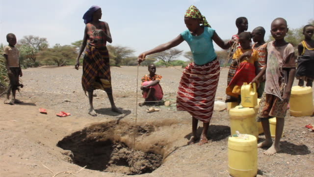 vídeos y material grabado en eventos de stock de ms pouring water into buckets near well / todonwang, turkana, kenya - sequía