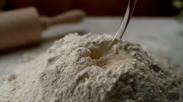 ケーキねり粉に水を注ぐ。超スローモーション - 混ぜる点の映像素材/bロール