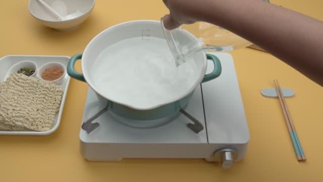 vídeos de stock e filmes b-roll de pouring water into cooking pot for making ramyun (korean instant noodle) - linha ondulada