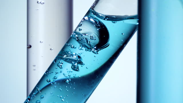 Pouring water into diagonally placed test tube with blue hue and movement of bubbles