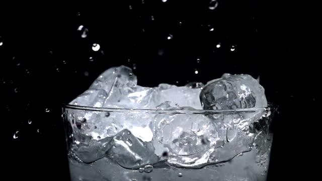 gießen wasser in glas mit eis mit akzenten in zeitlupe, auf schwarzem hintergrund - destilliertes wasser stock-videos und b-roll-filmmaterial