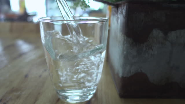 vídeos de stock e filmes b-roll de pouring water into glass sliding shot - copo vazio