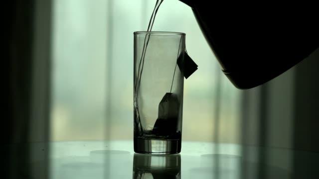 vídeos de stock, filmes e b-roll de pouring water into tea glass - preparação