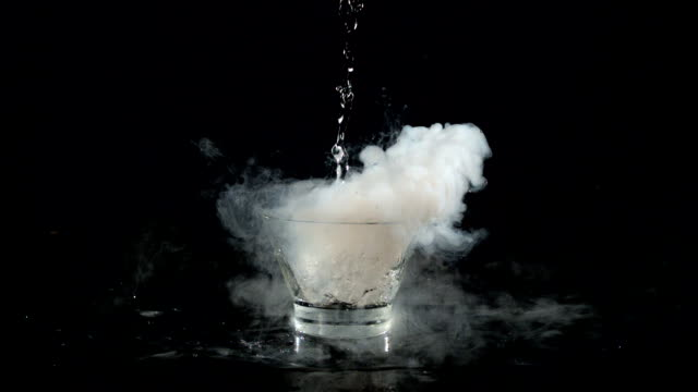 pouring water over dry ice. steam whirling around the glass - condensation stock videos & royalty-free footage