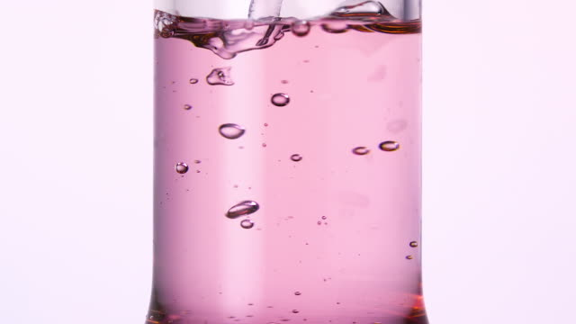 vidéos et rushes de pouring water produces bubbles in scientific glassware with pink water, slow motion - pink color