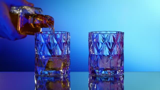 vidéos et rushes de verser le whisky de la bouteille dans le verre avec la glace - whisky
