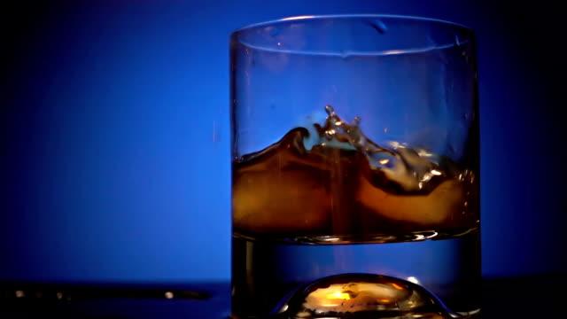 vidéos et rushes de verser le whisky avec des glaçons - glaçon