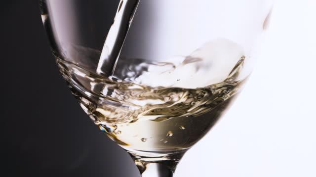 pouring white wine in to the glass - close up in slow motion - white wine stock videos & royalty-free footage