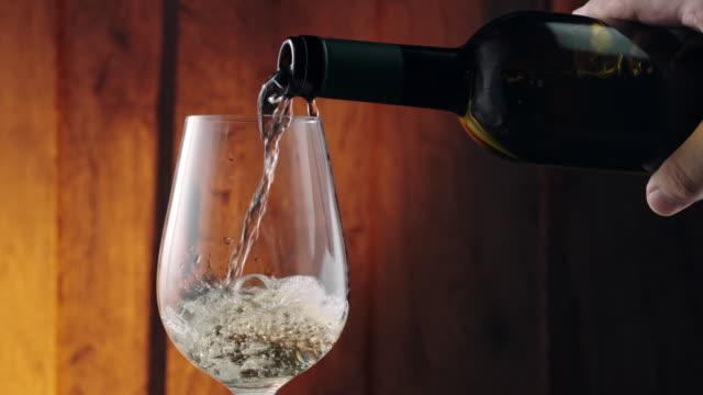 Weiße Wein gießen in ein Glas