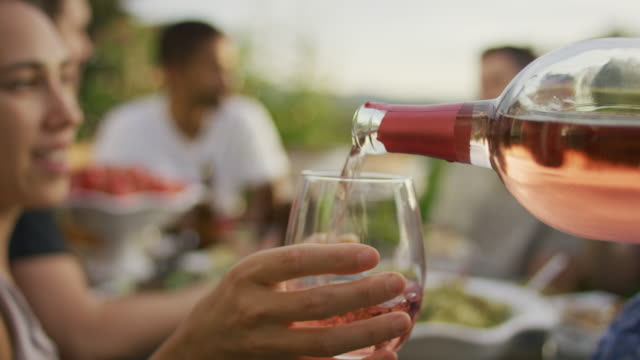gießt wein bei einem outdoor-dinner-party - patio stock-videos und b-roll-filmmaterial