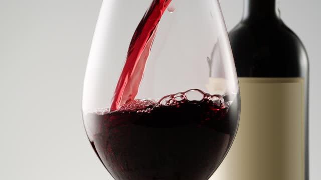 vidéos et rushes de verser le vin à l'intérieur du verre se ferment vers le haut - bouteille de vin