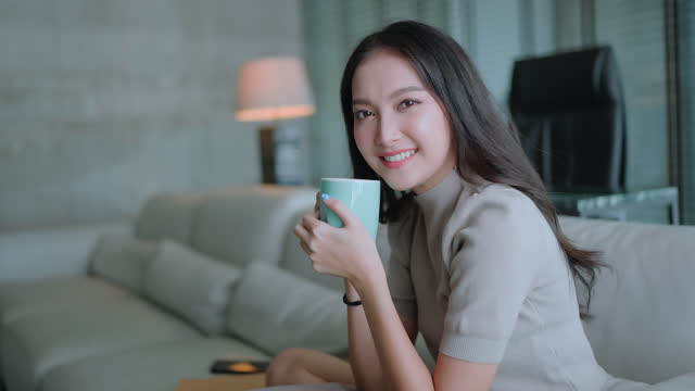 pov asian female woman hand hold coffee drink smile with cheerful and happiness sit on sofa couch at living room at home - armchair stock videos & royalty-free footage