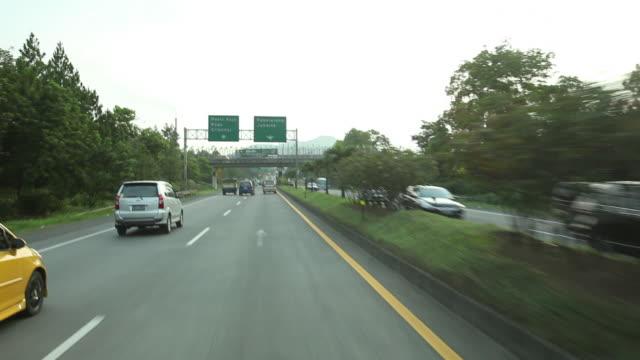 pov driving along motorway towards jakarta. - verkehrsschild stock-videos und b-roll-filmmaterial