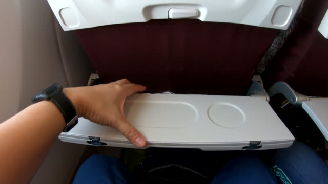 pov of hand open food tray infront of airplane seat while traveling - tray stock videos and b-roll footage