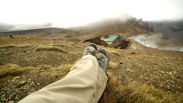 pov of hiker's legs relaxing by the mountain lake - tongariro national park stock videos & royalty-free footage