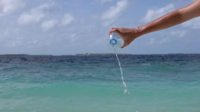 pov-ansicht einer hand, die eine plastikflasche gegen ein türkisfarbenes wasser hält - wasserflasche stock-videos und b-roll-filmmaterial