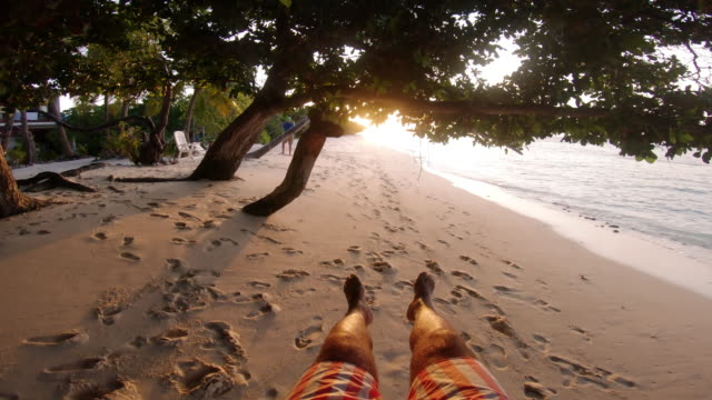 pov view of a young adult man while swinging on the beach at maldives - swinging stock videos & royalty-free footage